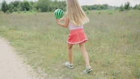 Girl playing with ball. A cheerful girl with a bow in her head, a striped t-shirt and a red polka dot skirt, plays with a watermelon ball, the game takes place stock footage