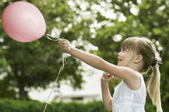 Girl Playing With Balloon In Garden Royalty Free Stock Photo