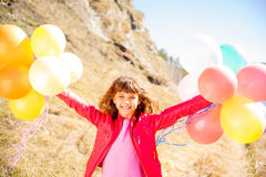 Girl playing with balloons Stock Images