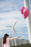 Girl Playing With Balloons At Wind Farm. Young girl playing with pink balloons near turbines at wind farm Stock Photo