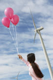 Girl Playing With Balloons At Wind Farm. Rear view of a young girl playing with pink balloons at wind farm Royalty Free Stock Photo