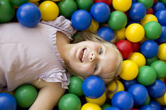Girl playing in the balls Royalty Free Stock Image