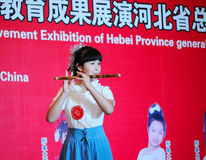 Girl in playing the bamboo flute Stock Photo