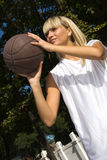Girl playing basketball outside. Young blond girl is playing basketball outside, aiming the basket Stock Photography
