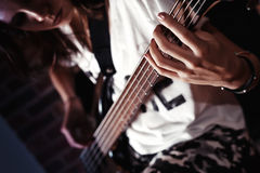 Girl playing Bass guitar indoor in dark room Royalty Free Stock Photos