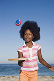 Girl (8-10) playing with bat and ball on sandy beach, smiling, front view, portrait Stock Images