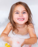 The girl playing in bath with foam. The child girl playing in bath with foam royalty free stock photos