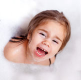 The girl playing in bath with foam. The child girl playing in bath with foam royalty free stock images