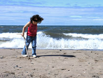 Girl playing on beach. Young girl playing on beach with waves in background Stock Photos