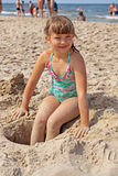 Girl playing on the beach. The construction of wells on the beach Royalty Free Stock Image