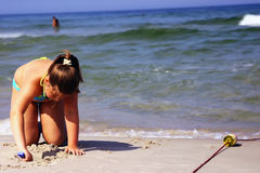 Girl playing on beach. Young girl digging into the sand on a beach, at the edge of the ocean surf Royalty Free Stock Images
