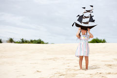 Girl playing on beach flying ship kite. Child enjoying summer. Stock Image