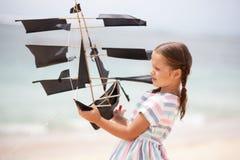 Girl playing on beach flying ship kite. Child enjoying summer. Stock Photos