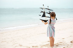 Girl playing on beach flying ship kite. Child enjoying summer. Cute little girl playing on the beach flying ship kite. Child enjoying summer family vacation at Royalty Free Stock Photos