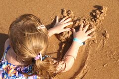 Girl playing on the beach with sand Covid - 19 Summer 2020