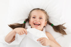 Girl playing in bed Royalty Free Stock Image