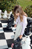 Girl playing big chess set. Girl moving a big chess piece Royalty Free Stock Photography