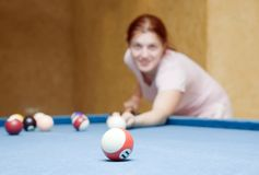 Girl playing billiards. Young woman playing billiards looking at camera. Focus on ball stock photos
