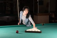 Girl playing billiards. woman holding the cue stick royalty free stock photos