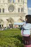 Girl playing with birds in the park next to Notre Dame Cathedral, Paris, France Stock Photo