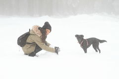Girl playing with black dog on snow Royalty Free Stock Photo