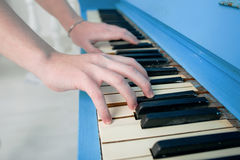 Girl playing blue piano Stock Photos