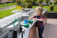 A girl playing with a boat in Madurodam. Little girl playing with a boat in Madurodam miniature city Stock Photo