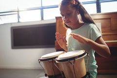 Girl playing bongo drums in classroom royalty free stock photos