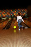 Girl playing bowling. In movement Royalty Free Stock Photos