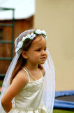 Girl playing bride. A cute little caucasian girl dressed in white like a bride playing wedding outdoors Royalty Free Stock Images