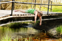 Girl Playing On Bridge. A young girl is leaning over a small bridge playing in the creek with a stick Stock Photography
