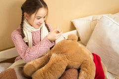Girl playing with brown teddy bear and making injection Stock Image