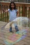 Girl Playing With Bubbles. Young girl plays outside with bubbles Royalty Free Stock Photography