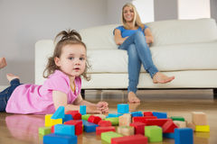 Girl playing with building blocks while mother on conch Royalty Free Stock Photos