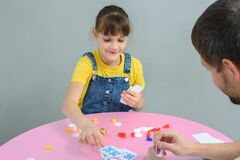 Girl playing card board games with dad