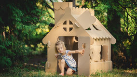 Girl playing cardboard house in a city park Stock Photos