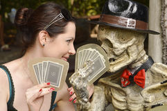 Girl playing cards with skeleton Stock Images