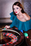 Girl playing in casino. Girl in sexy dress near the roulette Stock Photography