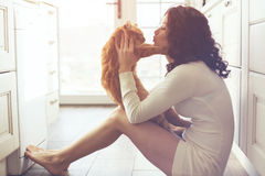 Girl playing with cat. Young lady kissing cat on the floor at the kitchen at home Royalty Free Stock Photos
