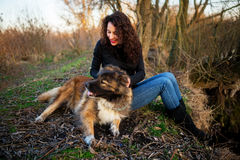 Girl playing with Caucasian shepherd dog, autumn. Young woman playing with Caucasian shepherd in a delightful spring day royalty free stock photos
