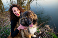 Girl playing with Caucasian shepherd dog, autumn. Young woman playing with Caucasian shepherd in a delightful spring day stock photos