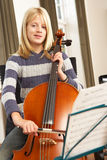 Girl playing cello at home Royalty Free Stock Photo