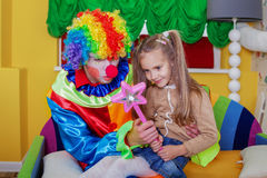 Girl playing with cheerful clown. Little girl playing with cheerful clown in funny costume. Friendship concept Royalty Free Stock Photos