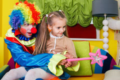 Girl playing with cheerful clown. Little girl playing with cheerful clown in funny costume. Friendship concept Royalty Free Stock Image