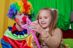Girl playing with cheerful clown Royalty Free Stock Photos