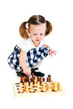 Girl playing chess. Cute little girl with ponytails playing chess. Isolated on white royalty free stock photography
