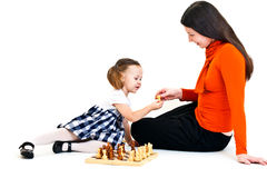 Girl playing chess. Cute little girl with ponytails playing chess with her mother. Isolated on white royalty free stock photo