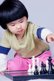 Girl playing chess. A picture of a little chinese girl playing chess alone Stock Image