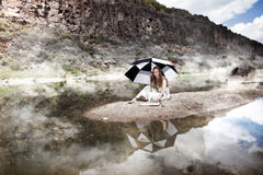 Girl playing chess alone. Under an umbrella by the river in morning fog and drizzle Royalty Free Stock Image