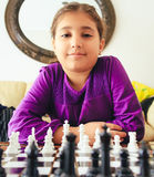 Girl playing chess. Cute happy girl playing chess Royalty Free Stock Photo